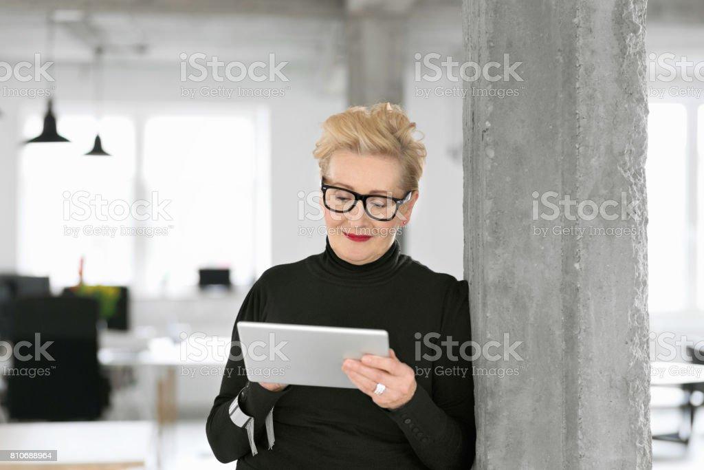 Elegant senior businesswoman using a digital tablet in the office Portrait of elegant senior businesswoman standing in her modern office and using a digital tablet. 60-69 Years Stock Photo