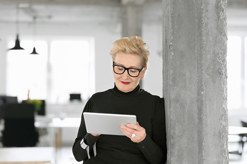 Elegant Senior Businesswoman Using A Digital Tablet In The Office Stock Photo - Download Image Now