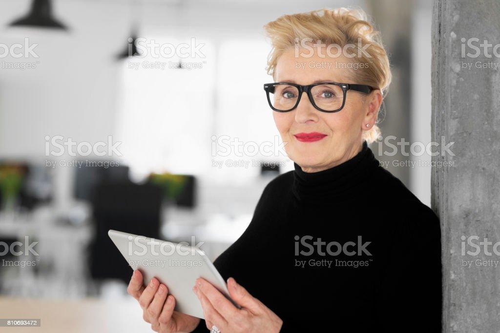 Elegant senior businesswoman using a digital tablet in the office Portrait of elegant senior businesswoman standing in her modern office and using a digital tablet, smiling at the camera. 60-69 Years Stock Photo