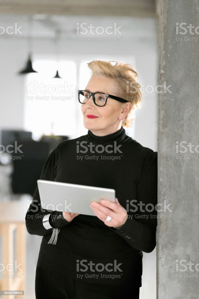 Elegant senior businesswoman using a digital tablet in the office Portrait of elegant senior businesswoman standing in her modern office and using a digital tablet. 60-69 Years Stock Photo