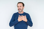 istock Elegant senior man over isolated background smiling with hands on chest with closed eyes and grateful gesture on face. Health concept. 1139078583