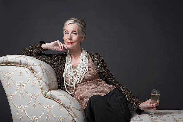 Elegant Senior Woman On Chaise Lounge With Champagne Portrait of an elegant senior woman sitting on chaise lounge with champagne against black background evening wear stock pictures, royalty-free photos & images