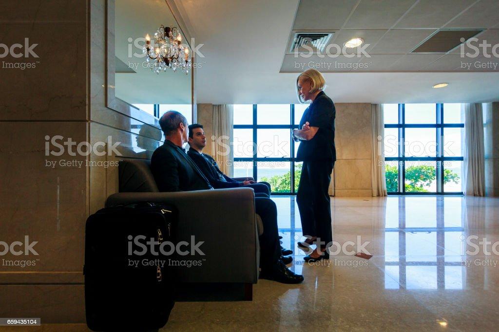 Elegant senior woman talking with work colleagues on a hotel lobby in Copacabana, Rio de Janeiro, Brazil. stock photo