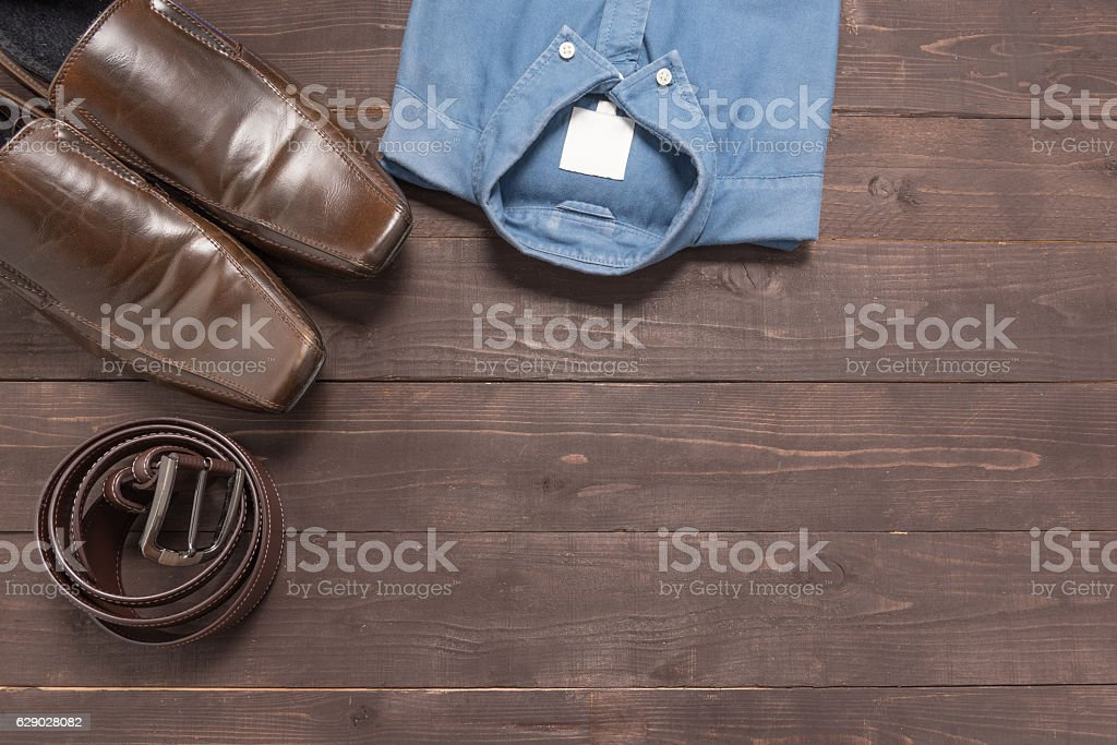 Elegant set: brown men's shoes, brown leather belt, blue shirt, stock photo