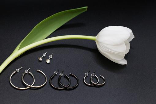 Elegant silver hoops earrings; with white tulip, black background