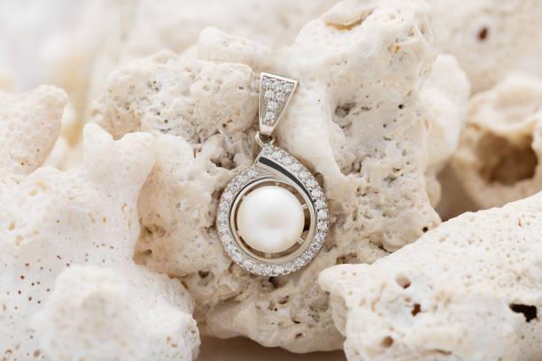 elegante silber anhänger halskette mit perlen und diamanten auf koralle - halskette weißgold stock-fotos und bilder