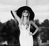 elegant smiling woman in black and white hat and dress