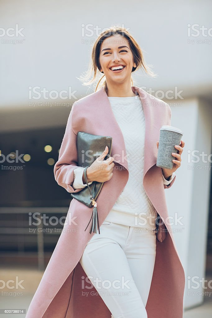 Elegant smiling woman walking outdoors stock photo