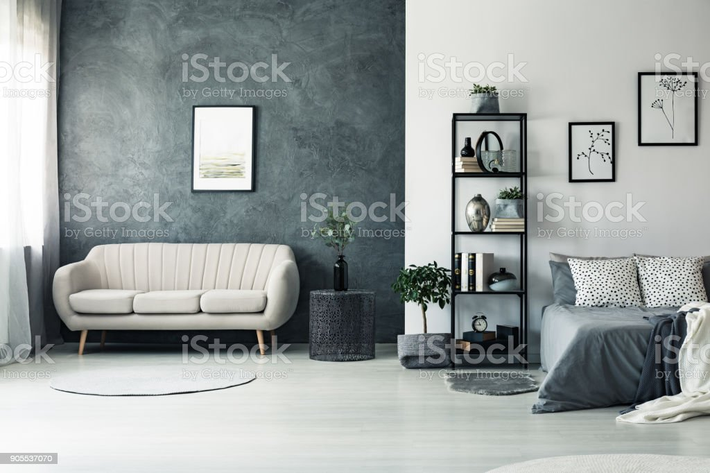 Elegant sofa standing by black wall stock photo