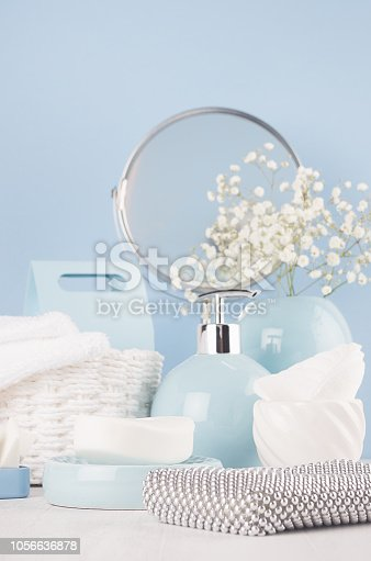 1056636898 istock photo Elegant soft bathroom dressing table with products for body and skin care, white flowers, towels, mirror, ceramic blue vase on white wood board, closeup. 1056636878