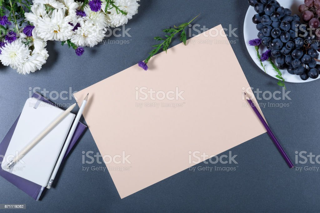 Elegant still life - sheet of beige paper, white and purple chrysanthemums, pencils, notebooks and plate with grapes on gray background. Beautiful romantic mock up. Top view. stock photo