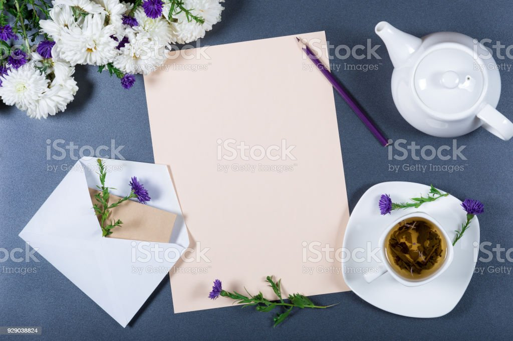 Elegant still life - sheet of paper, white and purple chrysanthemums, pencil, teapot, cup of herbal tea and envelope on gray background. Space for the text. Light romantic mockup. Top view. stock photo