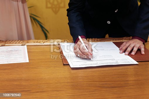 elegant stylish groom signing register, holding pen and official document. unusual luxury wedding couple in retro style. romantic moment