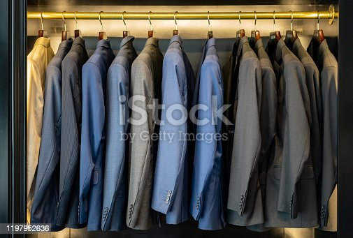 Elegant suits on coat hangers at a men's formal clothing store - Consumerism concepts