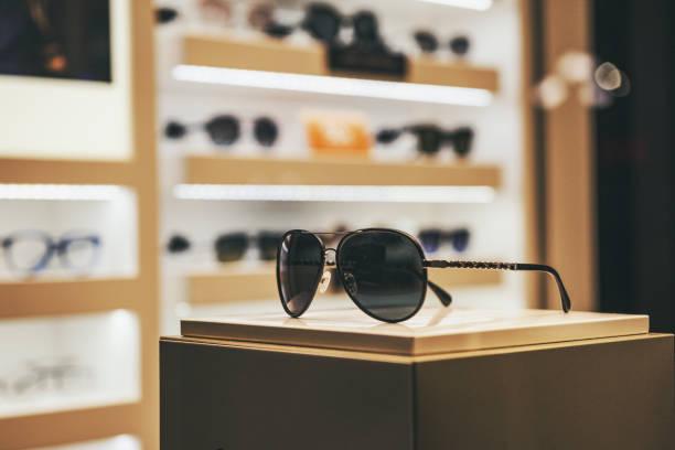 elegant sunglasses in a fashion store showcase - óculos escuros acessório ocular - fotografias e filmes do acervo