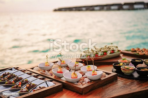 Elegant selection of gourmet tapas by the sea in the sunset