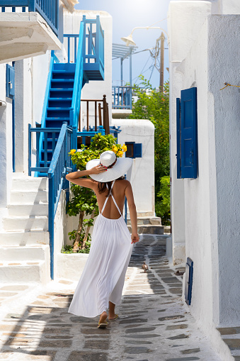 istock Elegant traveller woman walks through the town of Mykonos island 943642088