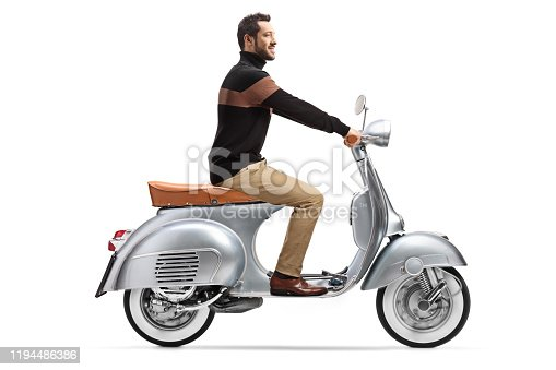 Full length profile shot of an elegant trendy man riding a silver vintage scooter isolated on white background