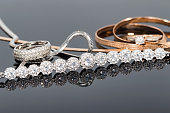 Silver and gold jewelry lie together on the reflective surface
