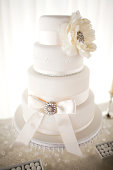 Elegant white wedding cake with bow and flower detail