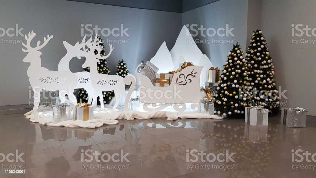 elegant white christmas decorations with deer silhouettes and ornate sleigh full with gift boxes wrapped in golden and silver papers near christmas trees winter holiday scene new year backdrop stock photo elegant white christmas decorations with deer silhouettes and ornate sleigh full with gift boxes wrapped in golden and silver papers near christmas trees winter holiday scene new year backdrop stock photo