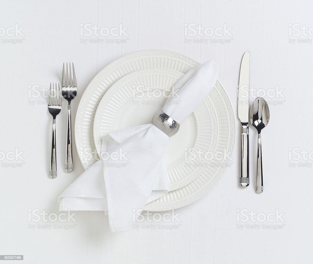 Elegant white dinner placesetting on white linen tablecloth royalty-free stock photo