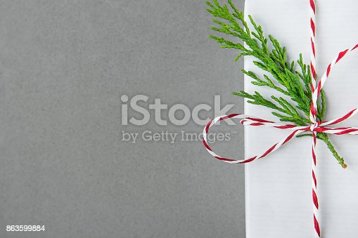 455111881 istock photo Elegant White Gift Box Tied with Red Ribbon Green Juniper Twig. Christmas New Years Presents Shopping Sale. Gray Background Copy Space 863599884