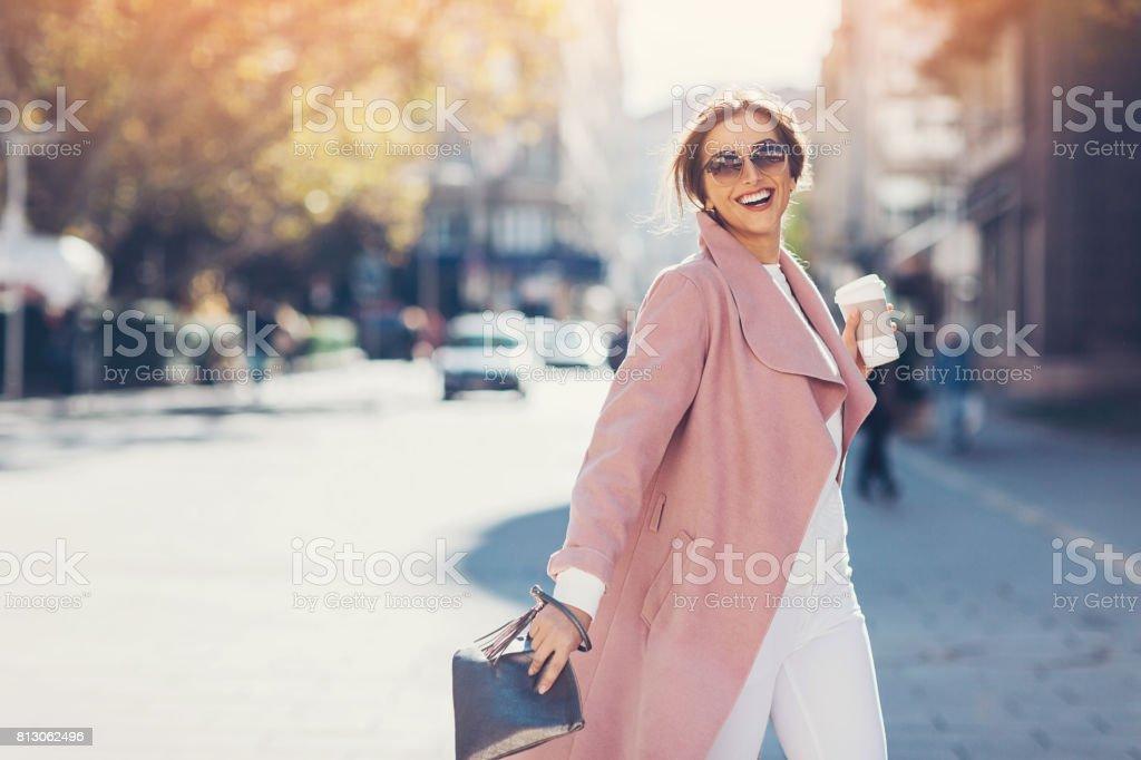 Elegant woman crossing the street stock photo