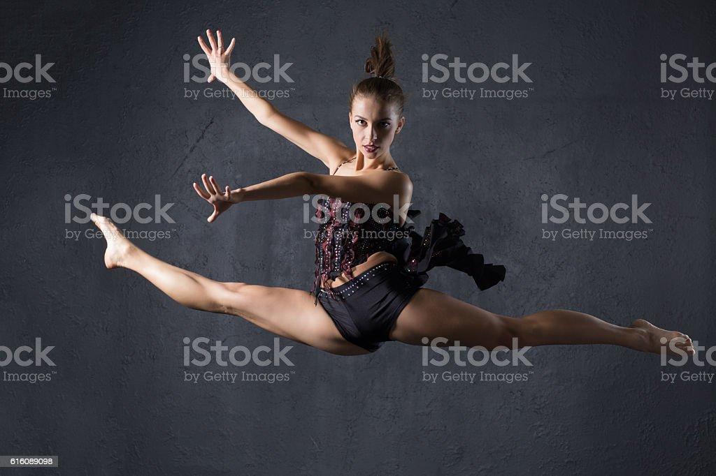 Elegant woman dance in dark studio stock photo