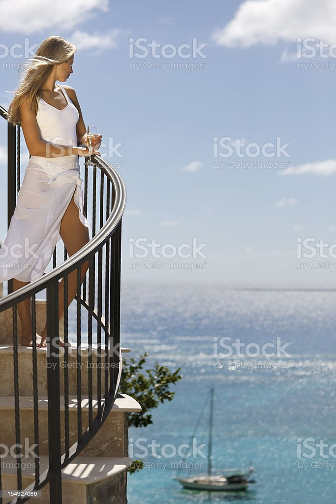 elegant woman enjoying a glass of champagne and Caribbean view royalty-free stock photo
