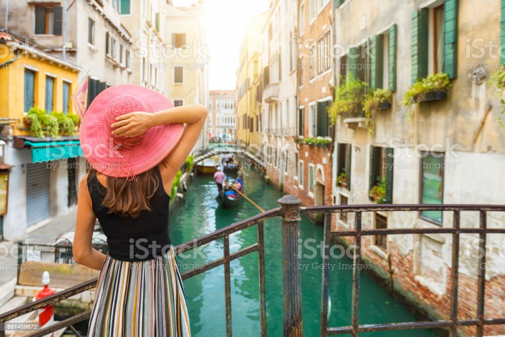 Elegant woman enjoys the view to a canal in Venice stock photo