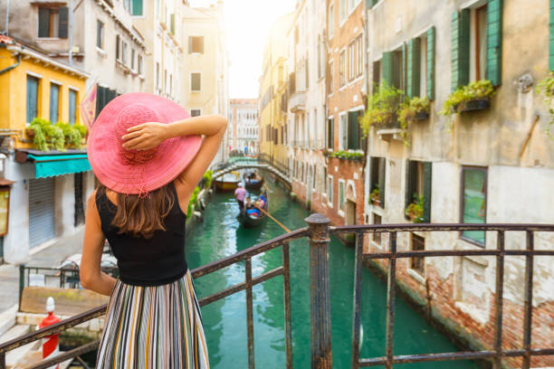 elegant woman enjoys the view to a canal in venice - tourism stock pictures, royalty-free photos & images