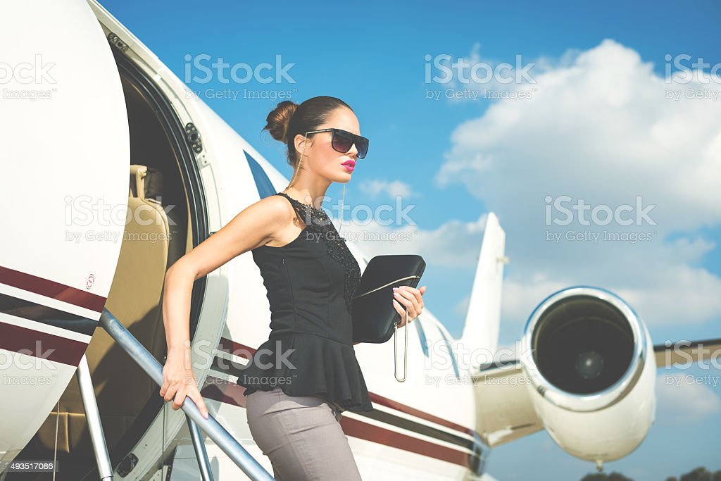 Elegant woman exiting private jet airplane stock photo