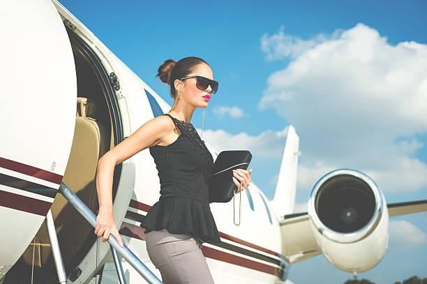 Elegant woman exiting private jet airplane stock photo