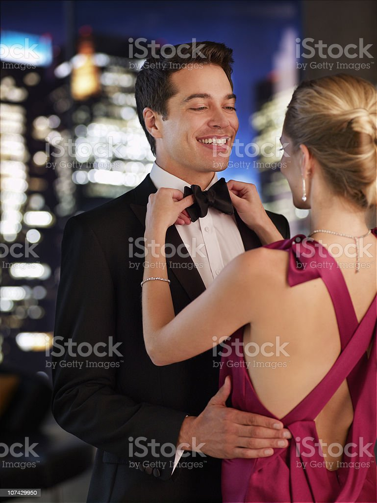 Elegant woman fixing husbands bowtie stock photo