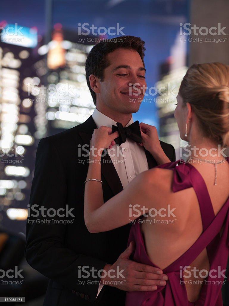 Elegant woman fixing husband's bowtie stock photo
