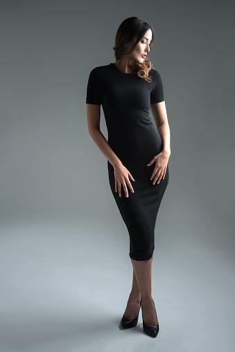 Fullbody elegant woman in a black dress in the studio - fashion concepts