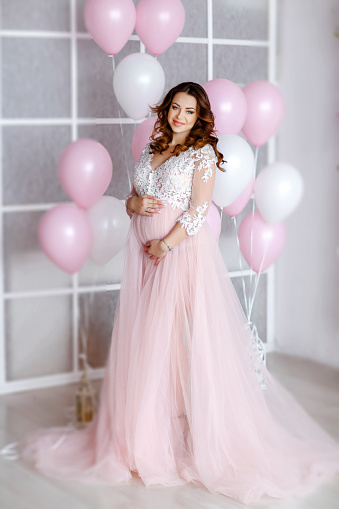 579443552 istock photo Elegant woman in a bride dress on a background of pink inflatable balloons 1200647962