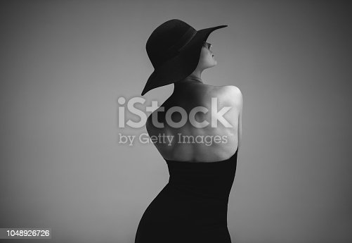Rear view of woman in black dress and hat against grey background. Monochrome shot of elegant woman posing in open back dress.