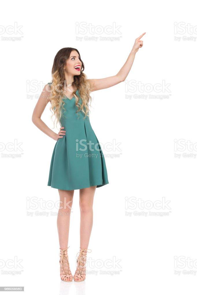 Elegante vrouw op hoge hakken staat, iets aan te raken en te lachen - Royalty-free Aanraken Stockfoto