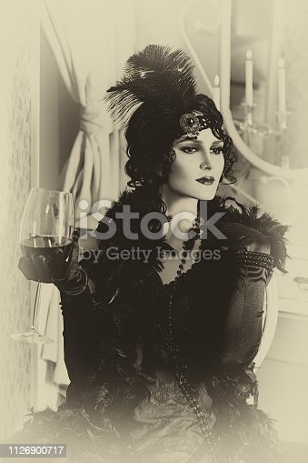 elegant woman in retro style of the 20s, lady flapper in a black dress, dark hair and a bandage, feather boa, long gloves. image of a gangster girl on a party, old fashion. art processing.