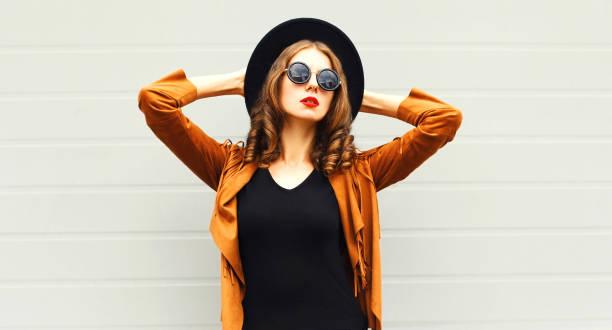 elegante frau modell trägt einen schwarzen hut, sonnenbrille und jacke über urbane grauen hintergrund - bedruckte leggings stock-fotos und bilder