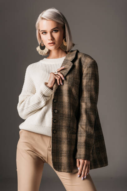 elegant woman posing in white sweater and autumn tweed jacket, on grey - giacca foto e immagini stock