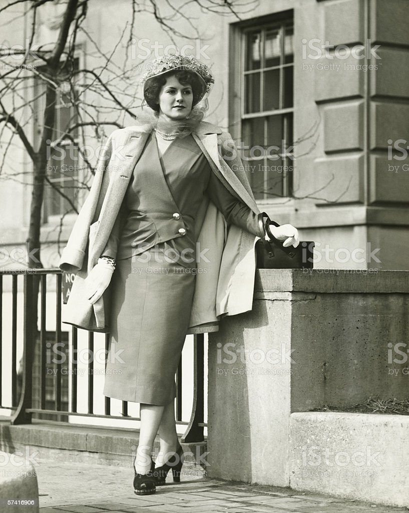 Elegant woman posing on sidewalk, (B&W) royalty-free stock photo
