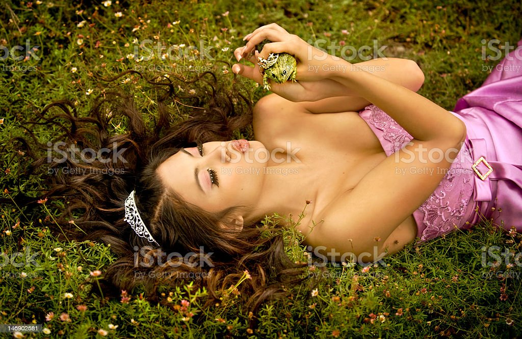 Elegant woman puckering up for frog while laying in grass stock photo