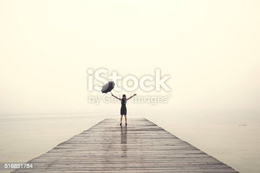 istock elegant woman rejoices with their arms up in the rain 516851784