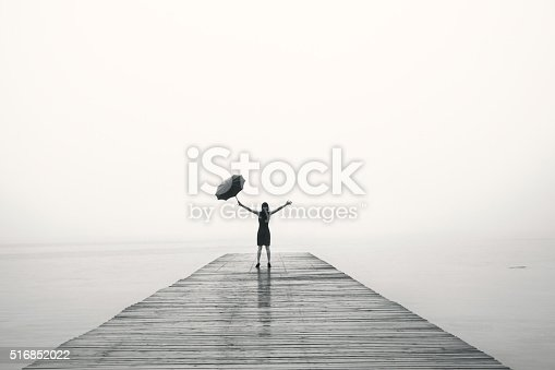 istock elegant woman rejoices with their arms up in the rain 516852022
