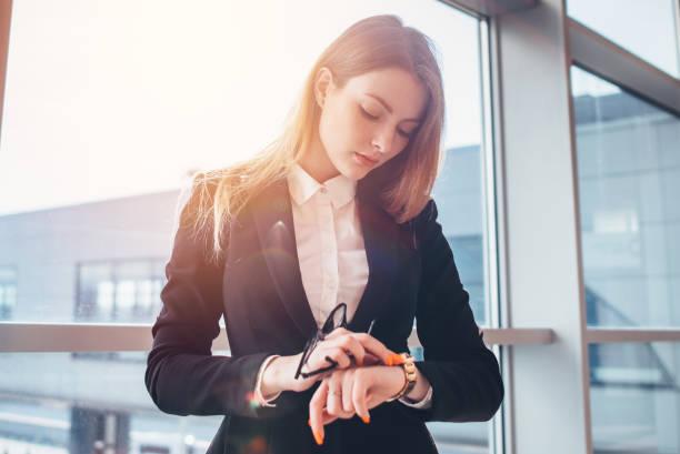 Elegante Dame, die Einstellung ihrer Uhr stehen im Flughafen – Foto