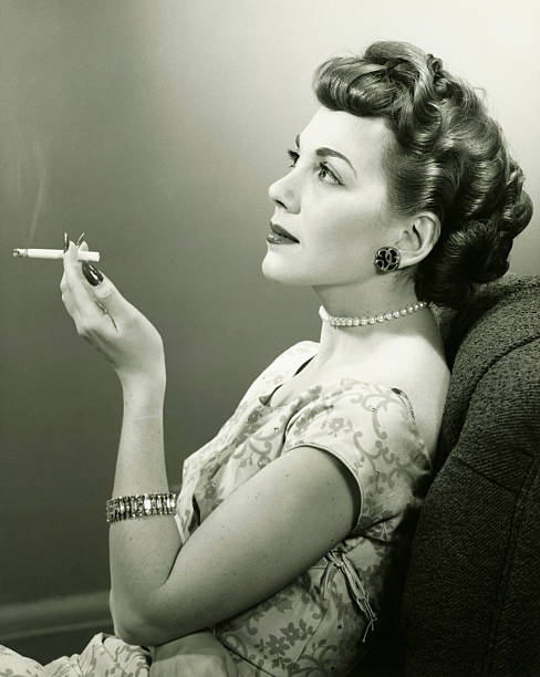 Elegant woman smoking cigarette, posing in studio, (B&W), portrait stock photo