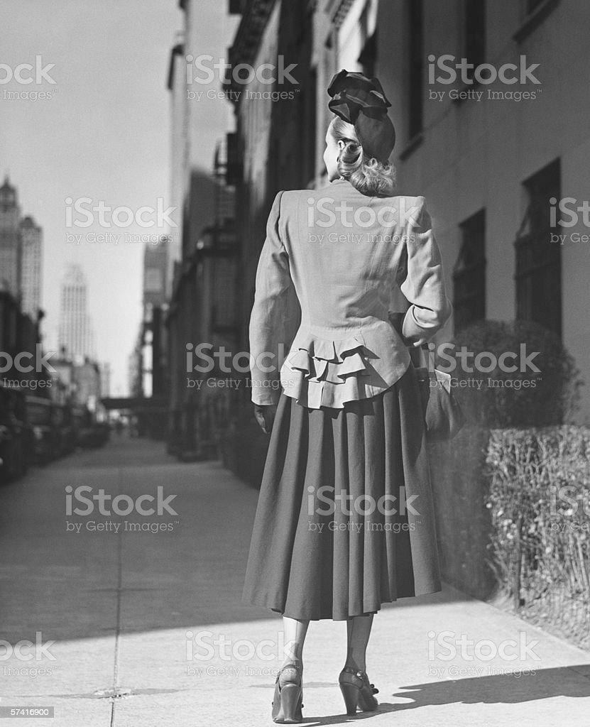 Elegant woman standing alone on sidewalk, Rear view, (B&W) stock photo
